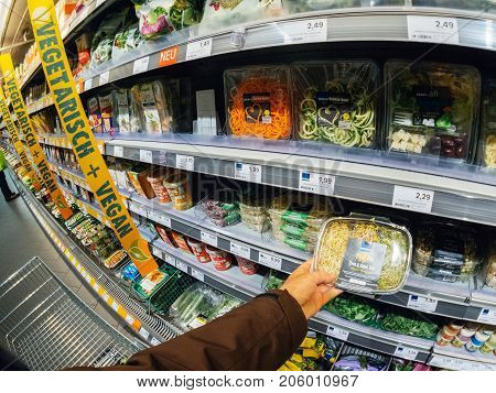 FRANKFURT GERMANY - MAY 3 2017: Male customer point of view buying vegan and vegetarian food in German supermarket Edeka - choosing the fresh carrots and salads for a healthy life