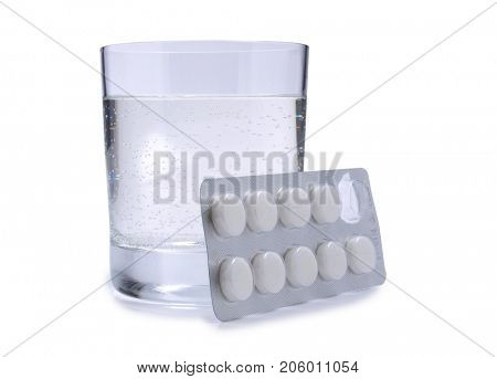 Medical pills and glass whit water on white background