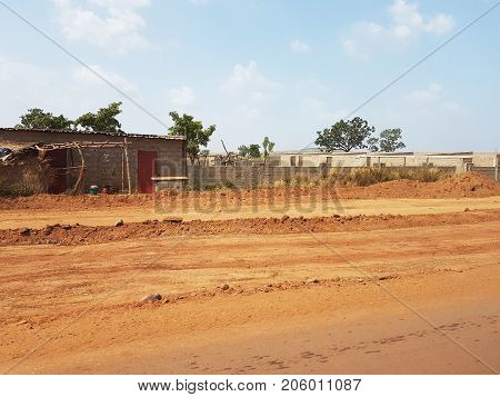 Generic poor street of Bamako Mali with small houses near the red African soil highway