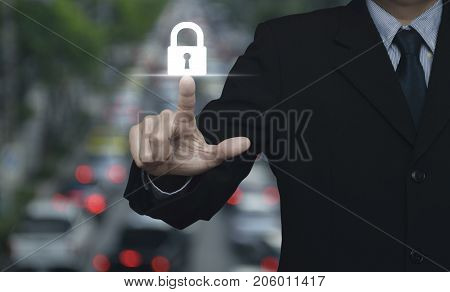 Businessman pressing key icon over blur of rush hour with cars and road Business security concept
