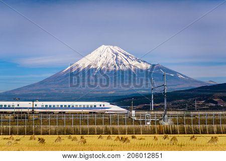 JAPAN - DECEMBER 14, 2012: A Shinkansen bullet train passes below Mt. Fuji in Japan.