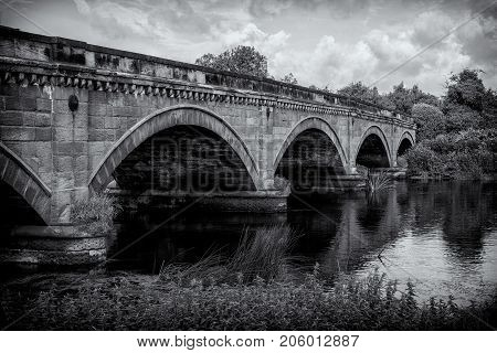 Stone Bridge over The River Trent between Repton and Willington Derbyshire. Showing the river cloudy sunny blue sky green folage foreground reflection of bridge in water.