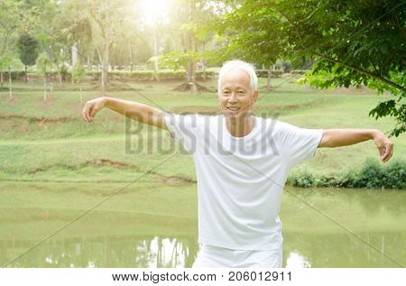 Portrait of healthy white hair Asian senior man practicing qigong at outdoor park in morning.