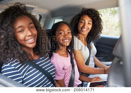 Portrait Of Family With Teenage Children In Car On Road Trip