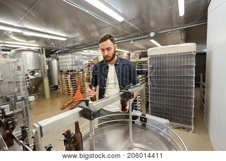 production, business and people concept - men with bottles on conveyor at craft brewery or non-alcoholic beverage plant