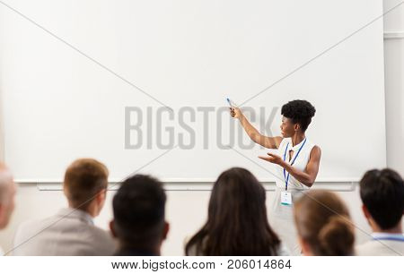 business, education and people concept - smiling african american businesswoman or teacher with marker showing something on screen to group of students at conference presentation or lecture