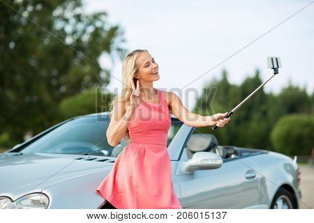 travel, road trip and people concept - happy young woman at convertible car taking picture by smartphone selfie stick and showing peace hand sign