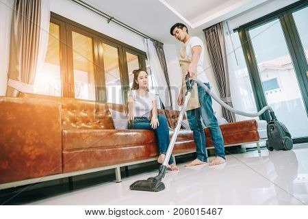 Asian teen couple are helping to clean the house. Man pointing Man ordered to clean up the area in front of the sofa. Man shows discontent