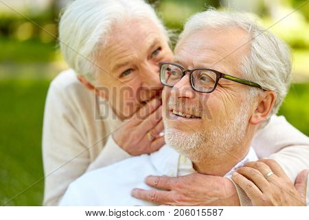 old age, retirement and people concept - close up of happy senior couple whispering outdoors