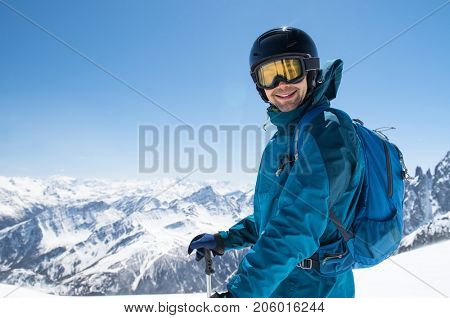 Cheerful skier looking at camera before starting to skiing. Happy man enjoying holiday in winter season. Smiling mountaineer skier in winterwear with ski equipment and copy space.
