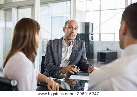 Mature financial agent showing new investment to young couple. Happy financial advisor discussing with a couple their mortgage loan. Happy couple consulting their bank agent about savings plan.