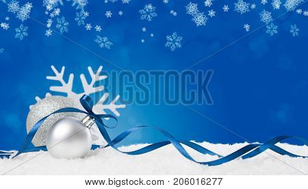 Christmas background in blue. Snow flakes and christmas balls with ribbon and copyspace. Xmas background with snowflakes, balls and ribbon. Write it on whatever you need.