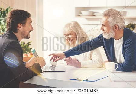 This one. Positive elderly couple sitting in the kitchen while meeting with their insurance agent