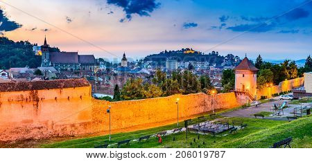 Brasov Romania - Twilight image with medieval city walled fortifications Black Church and the Citadel in Transylvania.