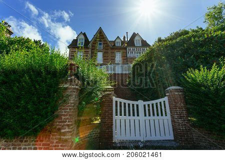 Country House With Green Fence And White Gate In Normandy, France On A Sunny Day With Sunbeam In Blu