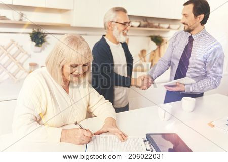 Come to agreement. Cheerful aged woman signing papers while her husband and real estate agent shaking hands while standing in the background