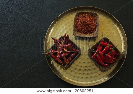 Overhead of red chilies, dried red chili pepper and crushed red pepper in plate