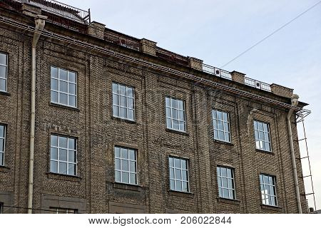 gray facade of an old high-rise building with windows on the sky background