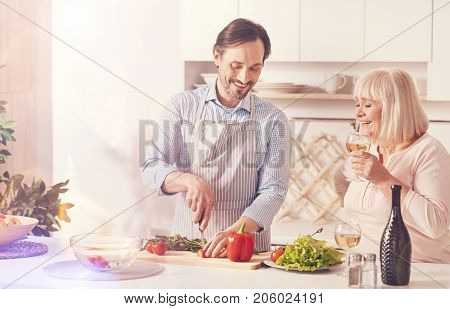 Family love. Cheeful adult man cutting vegetables and making salad while standing in the kitchen with his aged smiling mother