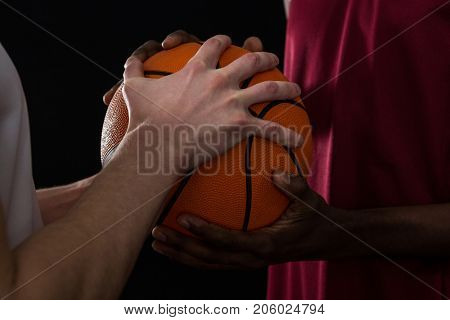 Mid section of competitors holding basketball against black background