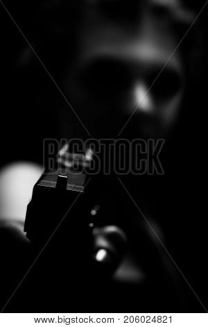 beautiful young woman with gun in dark aiming at camera, blurred monochrome image