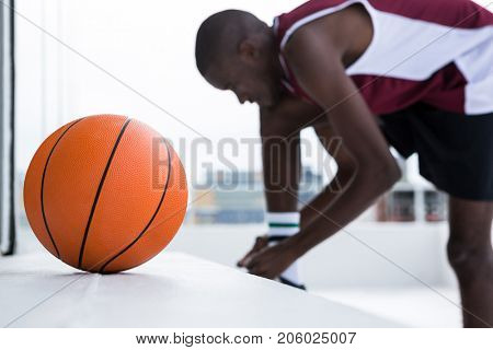 Determined basketball player tying shoelace