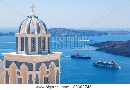 Sun shining through belltower of a church with a view of Santorini volcanic caldera and ships in it, Santorini, Cyclades, Greece