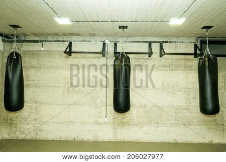 Three black punching bags in the empty boxing gym with naked grunge wall in background