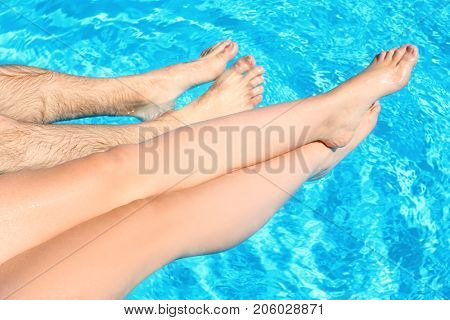 Couple soaking feet in swimming pool