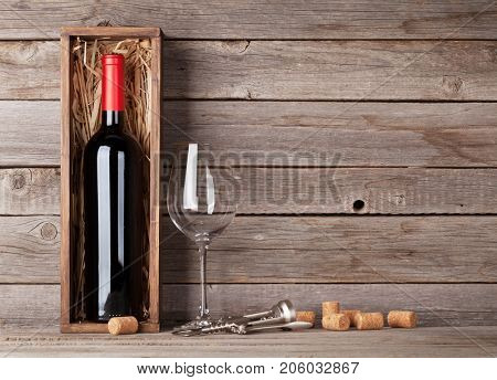 Red wine bottle in box and glass in front of wooden wall. With copy space