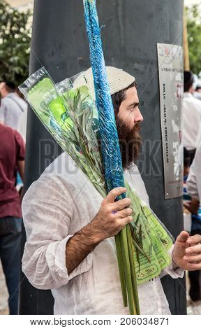 JERUSALEM, ISRAEL - OKTOBER 16, 2016: Traditional market before the holiday of Sukkot. Handsome Jew in knitted skullcap leaves the bazaar with purchases - myrtle, willow and lulav