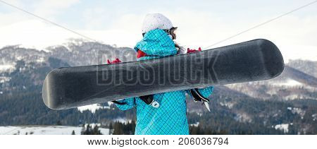 snowboarder girl standing hold snowboard in the blue sky