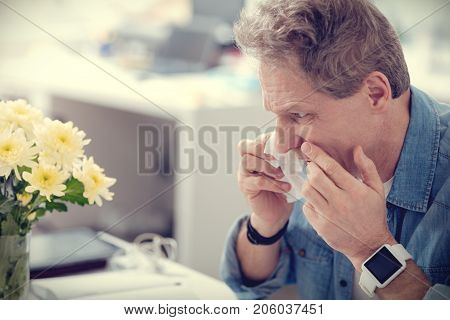 Allergic to flowers. Moody cheerless handsome man holding a paper tissue and having a running nose while sitting next to flowers