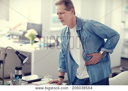 Acute appendicitis. Sad cheerless adult man feeling pain in his stomach and needing a doctor while having an acute appendicitis