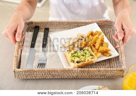 Woman holding wicker tray with dinner at table. Cooking for one concept