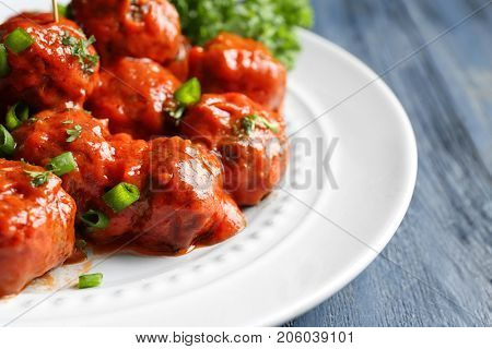 Plate with delicious meatballs on wooden table