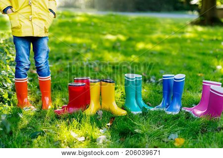 Little kid, boy or girl in jeans and yellow jacket in colorful rain boots. Close-up of child with different rubber boots. Footwear for rainy fall. Concept of bright autumn