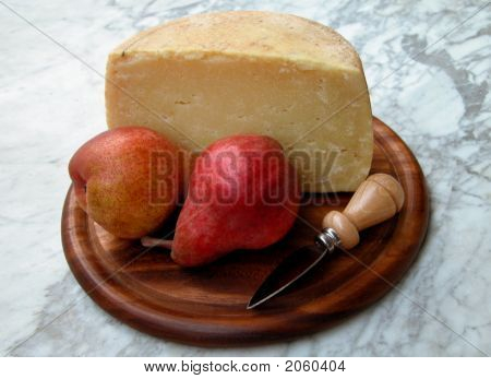 Two Red Pears And A Piece Of Cheese On A Wooden Tray