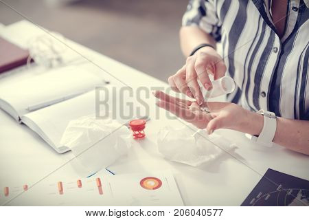 Unpleasant illness. Close up of a table of a nice professional ill woman with paper tissues and medicine on it