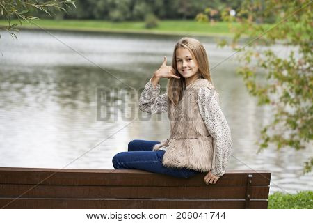 Sign Call me. Pretty blonde litte girl, autumn park outdoors