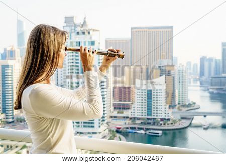 Woman is looking at a city with spyglass from her balcony