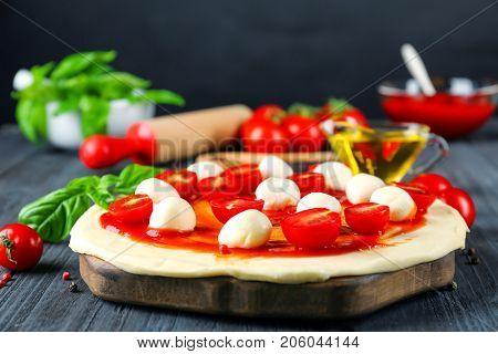 Uncooked pizza with cherry tomatoes, mozzarella cheese and fresh basil on kitchen table