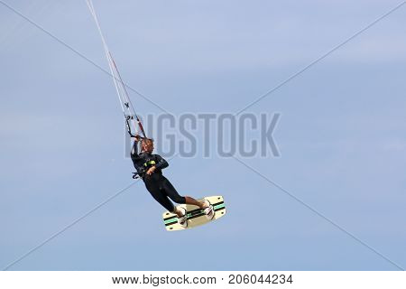 kitesurfer man jumping high on his board