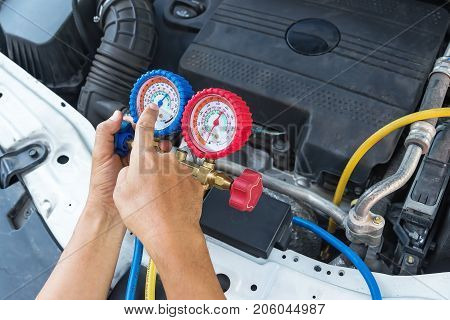Auto mechanic using digital multimeter to check the fuse in a carcheck voltage level car battery.