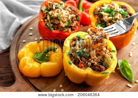 Eating of quinoa stuffed pepper on wooden board