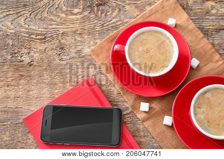 Cups of aromatic morning coffee and phone on table