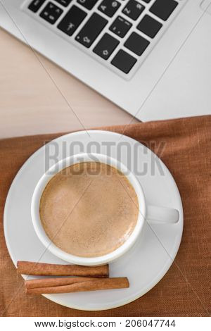 Cup of aromatic morning coffee with cinnamon sticks on table