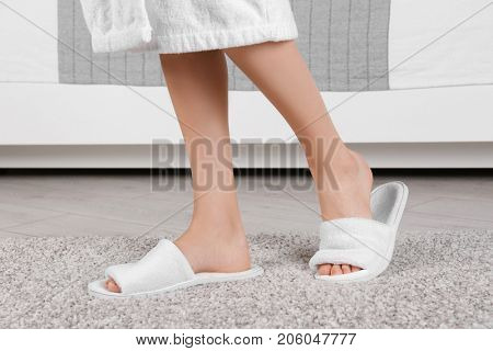 Woman standing in white spa slippers on grey fuzzy carpet