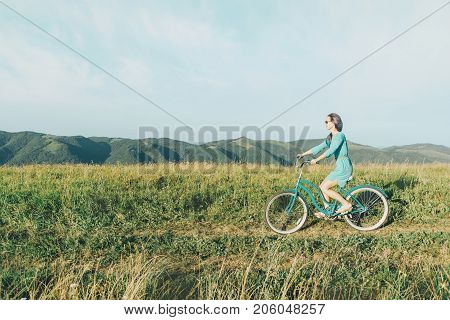 Beautiful young woman wearing in dress riding bicycle on summer meadow side view.