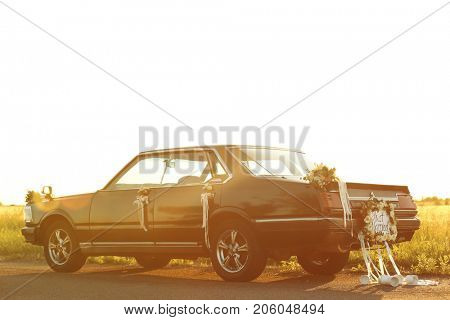 Beautiful wedding car with plate JUST MARRIED and cans outdoors